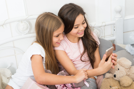 Writing their Christmas greeting sms. Merry Christmas and Happy New Year. Texting Christmas and New Year greetings by phone. Happy small children with mobile phone. Small girls use smartphone in bed. Stock Photo