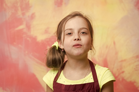 Baby girl posing with mouth full of food on abstract colorful wall. Enjoy delicious cuisine concept. Healthy eating and dieting. Child and childhood.