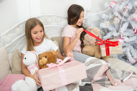 Being so excited for Christmas morning. Merry Christmas and Happy New Year. Happy small children hold gift boxes. Opening presents on Christmas. Small girls with presents in bed. New Year surprise.