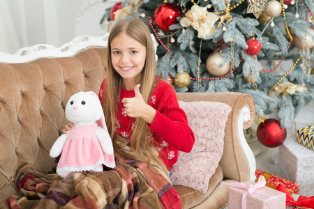 I like it very much. Little girl thumbs up to cute bunny at Christmas tree. Small girl hold rabbit toy. Little child play with soft toy. Small child happy smiling with present. Best Christmas toy.