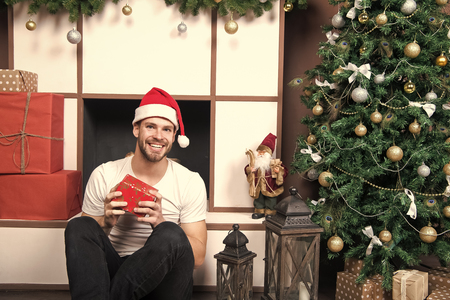 Macho smile with present box at Christmas tree. Winter holidays preparation and celebration. Boxing day concept. xmas and new year room interior. Man in santa hat sit at fireplace. 免版税图像