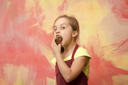 Healthy food and diet concept. Baking and delicious bakery. Girl eating cupcake. Child biting cake. Baby cook in red chef apron on colorful abstract wall. Standard-Bild - 120907903