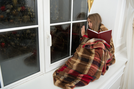 Once upon a time. Small girl enjoy reading Christmas story. Small child read book on Christmas eve. Small reader wrapped in plaid sit on window sill. Childrens picture book. Magic xmas spirit. 版權商用圖片