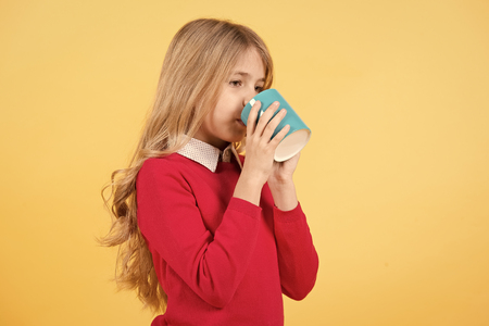 Girl drink tea or coffee from cup with long blond hair in red sweater on orange background. Thirst, dehydration concept. Standard-Bild - 120907906