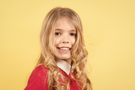 Child with curly blond hair on orange background. Girl with smile on cute face. Beauty, youth, fashion. Happy childhood concept. Look, style, hairstyle, copy space Standard-Bild - 120907908