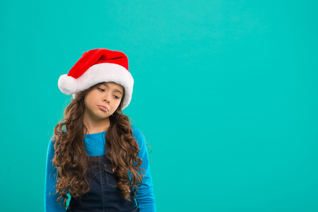 New year party. Santa claus kid. Present for Xmas. Childhood. Happy winter holidays. Small sad girl. Christmas shopping. Little girl child in santa hat. Feast of Christmas. By golly, be jolly.