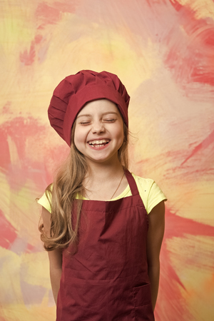 Kid cook smiling on colorful wall. Girl in chef hat and apron. Cooking and playing. Child and happy childhood. Career, uniform, dream, occupation and profession concept. Standard-Bild - 120907953