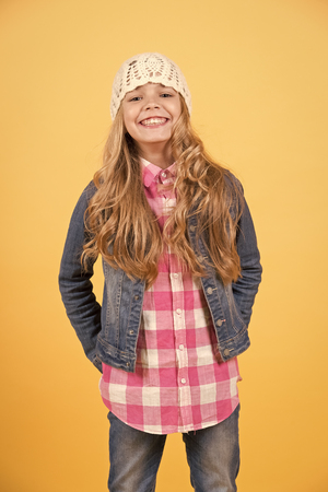 Beauty, look, hairstyle. Girl in jeans suit, hat, plaid shirt on orange background. Fashion, style, trend. Child smile with long blond hair. Happy childhood concept Standard-Bild - 120907954