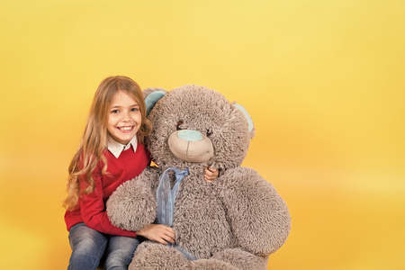 Kid with animal doll, present and gift. Girl sit with big teddy bear on orange background. Holiday, birthday, anniversary celebration. Child smile with grey soft toy. Happy childhood concept. Standard-Bild - 120907955