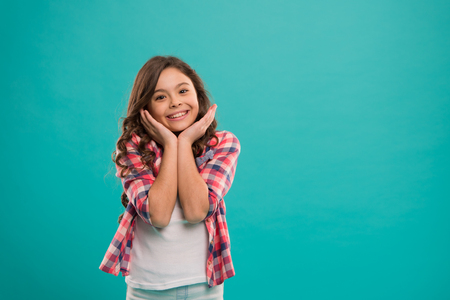 Kid happy cute face with adorable curly hair stand over blue background. Pure beauty. Beauty tips for tidy hair. Kid girl long healthy shiny hair wear casual clothes. Little girl with long hair. Standard-Bild - 120907962