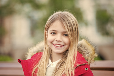 Kid enjoy autumn day. Leisure, relaxation, lifestyle. Child with blond long hair smile outdoor. Happy childhood concept. Girl in red coat sit on bench in park. Standard-Bild - 120907966