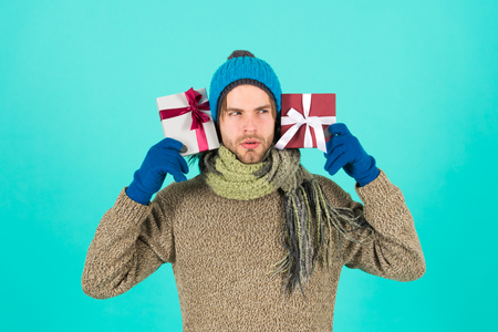 What is inside. Man bearded handsome wear winter hat scarf gloves hold two gift boxes. Hipster hold christmas gift with bow. Holiday present concept. Winter holidays. Give gift spread happiness. Standard-Bild - 120907982