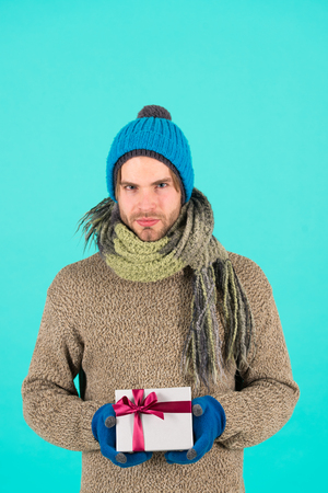 I have something for you. Man bearded handsome wear winter hat scarf gloves hold gift box. Hipster hold christmas gift with bow. Holiday present concept. Winter holidays. Give gift spread happiness. Standard-Bild - 120907985