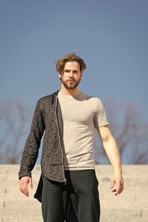 Man with beard wear tshirt on sunny outdoor, fashion. Macho stand on blue sky, perspective. Mens fashion and style. Perspective, future, freedom. Standard-Bild - 120907987