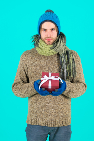 Man bearded handsome wear winter hat scarf gloves hold gift box. Hipster hold christmas gift with bow. Holiday present concept. Winter holidays. Give gift spread happiness. I have something for you. Standard-Bild - 120907988
