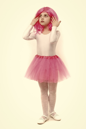 Small girl t in pink skirt. beauty and fashion. Childhood and happiness. Child in wig isolated on white background. ballet and art. Standard-Bild - 120907989