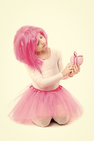 Holiday celebration and mothers day. Christmas and birthday. Childhood and happiness. Child in wig isolated on white background. Small girl with valentines heart in pink skirt. Standard-Bild - 120907991