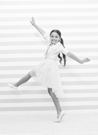 Child concept. Happy little child dancing. Child girl smile in fashion dress. Child and childhood. sense of freedom. Standard-Bild - 120907993