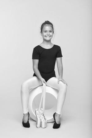 Ginnasta flessibile per bambini che si esercitano in punta di piedi. Il tenero ballerino sembra un magnifico body fantasia. Sogna che ogni ragazza diventi una ginnasta famosa. Kid sit hold scarpe da ballo da punta. Scarpe speciali per il balletto. Archivio Fotografico