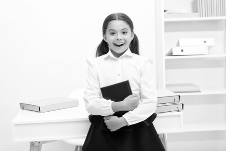 Happy to enter into first form. Girl child holds book stand near table white background. Schoolgirl enjoy studying and visiting lessons. Kid school uniform smiling face likes visiting school lessons. Standard-Bild - 120908008