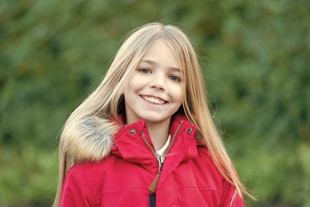 Innocence, purity and youth. Girl with blond long hair smile on natural environment. Beauty, nature, growth. Child in red coat enjoy idyllic autumn day. Happy childhood concept. Standard-Bild - 120908009