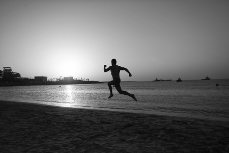 Silhouette man motion running in front of sunset sky above sea surface. Never stop. Future success depends on your efforts now. Daily motivation. Healthy lifestyle personal achievement and success. Standard-Bild - 120908013