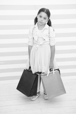 Shopping tiring exhausting activity. Child carries shopping bags striped background. Kid girl spend day buy things supplies for school. Back to school sales season. Girl exhausted holds bags. Standard-Bild - 120908015