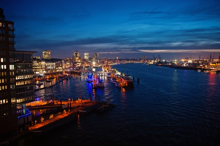 Sea port with ships and cranes in Hamburg, Germany with light illumination at night.