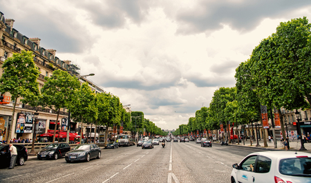 Paris, France - June 02, 2017: Elysian Fields avenue with street traffic and green trees on cloudy sky background. Landmark and sightseeing. Summer vacation and travel concept, triumphal arch road Reklamní fotografie