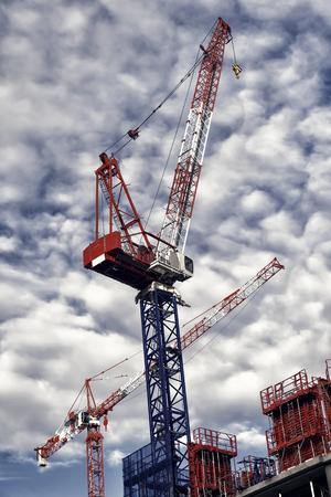 Construction cranes on site in business district of la defense, paris, france on cloudy sky. Reklamní fotografie
