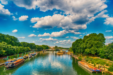 River and bridge in Paris, France on sunny day on cloudy blue sky