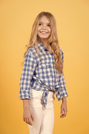 Girl with long blond hair smile on orange background. Girl happy smiling in shirt and pants. Foto de archivo