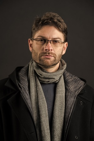Man in glasses on bearded face. Businessman in scarf and coat on grey background. Fashion, eyewear, accessory. Vision, business, future concept. Eyesight correction, eye care, health