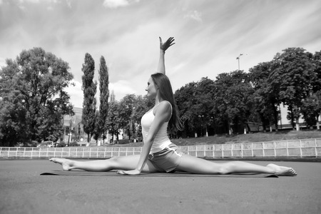 Split is easy for her. Stretching muscles every time training. Coach tips and advice. Woman flexible body practice split on fitness mat outdoors nature background. Girl stretching legs after workout. Reklamní fotografie - 123301897