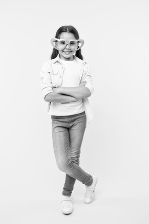 Kid girl heart shaped eyeglasses look confident. Girl wear cute eyeglasses confident face. Child confident cheerful posing folded arms. She know how stay positive any situation. Confident posture.