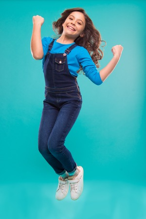 International childrens day. small kid fashion. Childhood happiness. small girl child with perfect hair. Happy little girl. Beauty and fashion. i am a champion. jump for free. Imagens
