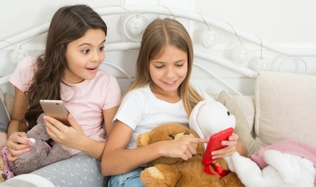 It cant be true. Happy little children with mobile phone. Merry Christmas and Happy New Year greetings. Little girls use smartphone in bed. Ordering gifts for Christmas and New Year by phone.
