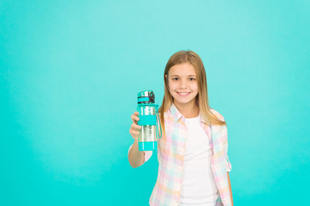 Water balance concept. Healthy and hydrated. Pediatric disorders of water balance. Girl cares about health and water balance. Child girl long hair has water bottle. Kid hold bottle blue background. Фото со стока
