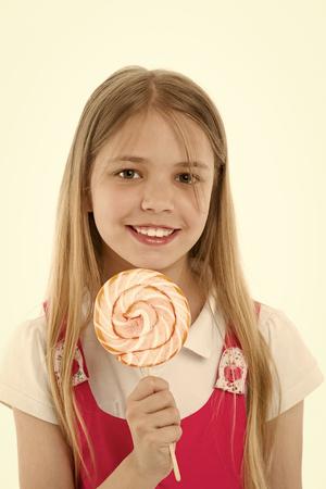 Mädchenlächeln mit Lutscher getrennt auf Weiß. Kleines Kind, das mit Süßigkeiten auf Stick lächelt. Glückliches Kind mit Strudelkaramell. Essen und Dessert. Genießen Sie süßen Lutscher. Diät und Diät. Standard-Bild