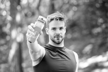 Towards a healthier lifestyle. Athlete drink water after training in park. Man athletic appearance holds bottle with water. Man athlete cares about water balance. Sport and healthy lifestyle.