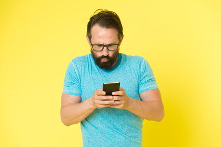 Hipster puzzled use smartphone. Man inexperienced user of modern smartphone. Stay in touch with smartphone. Join online community. User friendly concept. Man puzzled mobile phone opportunities.