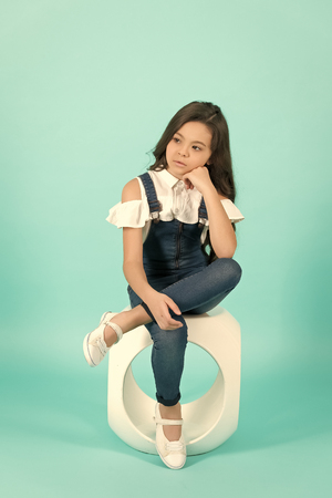 Child with thinking face sit on chair on blue background. Preteen model with long brunette hair in jeans overall. Kid fashion, style. Beauty, look concept. Youth, skincare, health.