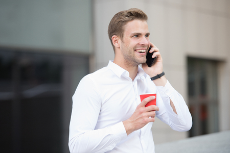Man drink coffee speak phone urban background. Drink coffee. Each sip is moment of self care. Reasons entrepreneurs drink coffee. Coffee break concept. Relax and pleasure. Call friend share news. Stock Photo