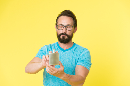How choose perfume for men according to occasion. Make sure smell fresh throughout day. Amazing benefits of using perfumes. Man bearded handsome hold bottle perfume. Wearing perfume is enhancing mood.
