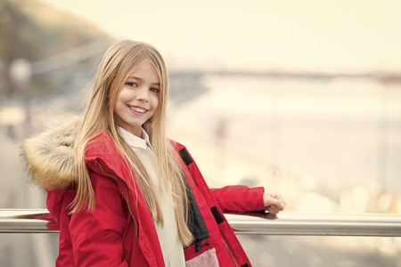 Girl with blond long hair smile outdoor. Child in red coat stand on bridge. Adventure, discovery, journey. Kid enjoy autumn day on blurred urban landscape. Vacation, travelling concept.