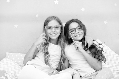 Birthday girl. Children posing with grimaces photo booth props. Pajamas party in bedroom. Friends cute and cheerful posing with eyeglasses accessories. Girls friends having fun pajamas party. Stock Photo