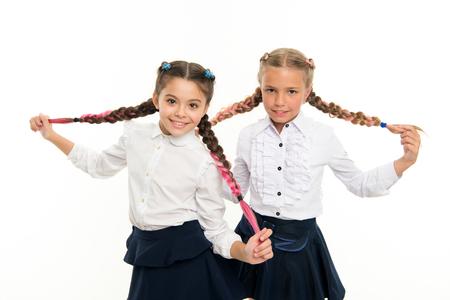 Schoolgirls wear formal school uniform. Sisters little girls with braids ready for school. School fashion concept. Be bright. School friendship. Sisterhood relationship and soulmates. On same wave.