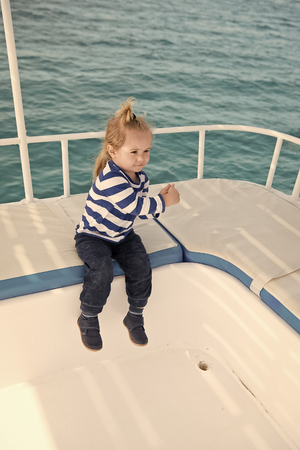 Summer vacation concept. Boy in sailor shirt sail in blue sea. Adventure, discovery, wanderlust. Child with blond hair on yacht on sunny day. Travel destination, cruise, travelling. 写真素材 - 120802529