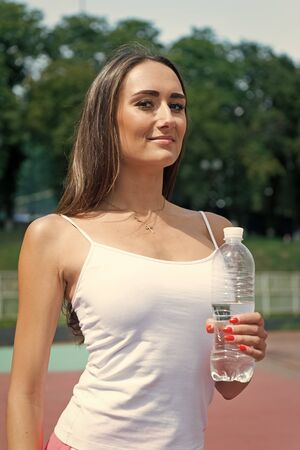 Woman drink water from bottle. Girl sunny outdoor. Summer activity and energy. coach relax after workout. Sport and health.