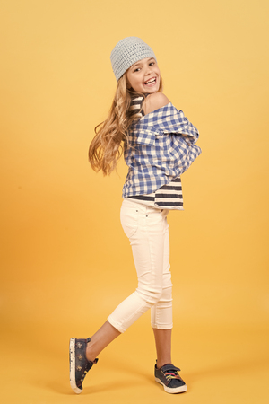 Child smiling with long blond hair, beauty. Small girl smile in hat, shirt and pants, fashion. Kid fashion, beauty, style. Happy childhood, youth. Punchy pastel trend 版權商用圖片